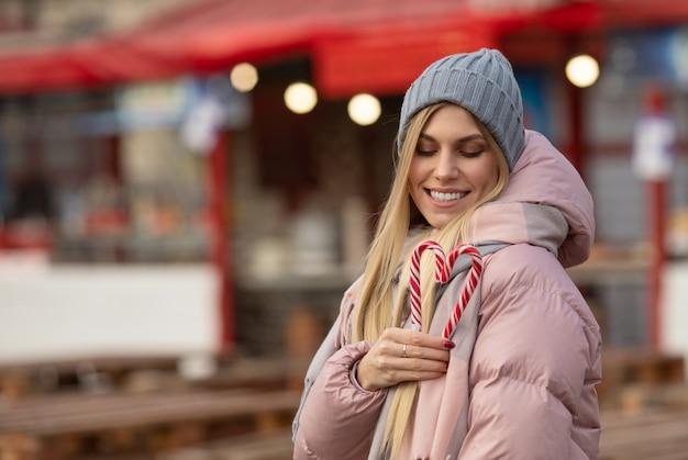 Portrait d'une belle jeune femme heureuse avec des bonbons posant dans la rue d'une ville européenne. noël.