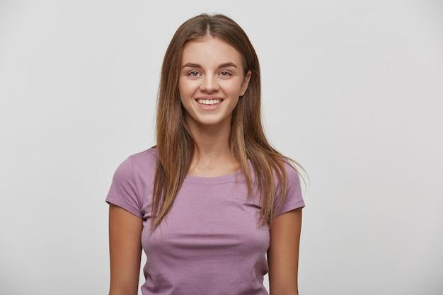 Portrait d'une belle jeune femme heureuse joyeuse avec un maquillage naturel et des cheveux bien coiffés, sourit, porte un tshirt décontracté