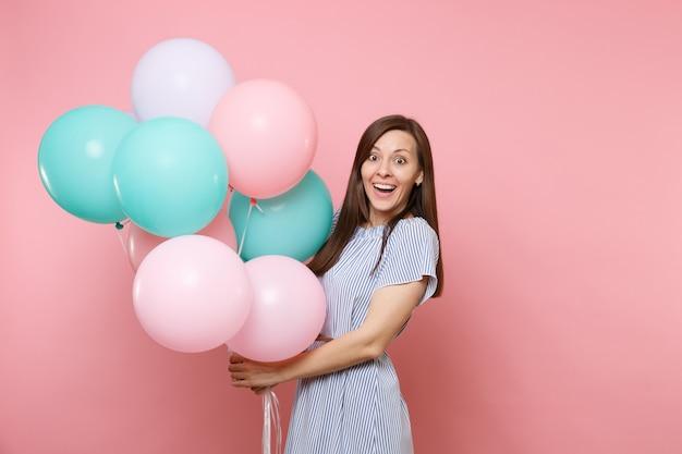 Portrait de la belle jeune femme heureuse joyeuse vêtue d'une robe bleue tenant des ballons à air colorés isolés sur un fond rose tendance lumineux. fête d'anniversaire, concept d'émotions sincères.