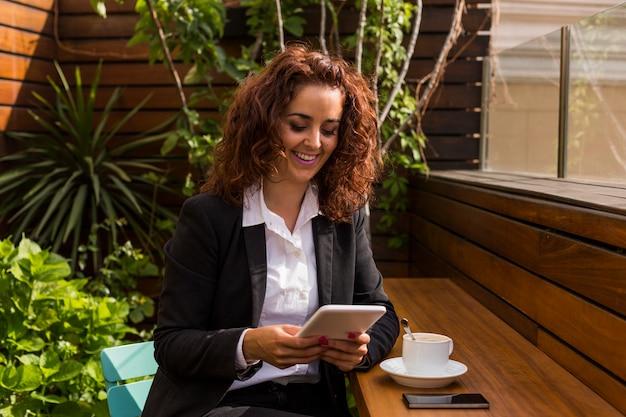 Portrait d'une belle jeune femme heureuse souriant et en utilisant sa tablette. femme d'affaires sur une terrasse le matin. l'heure du café. pause