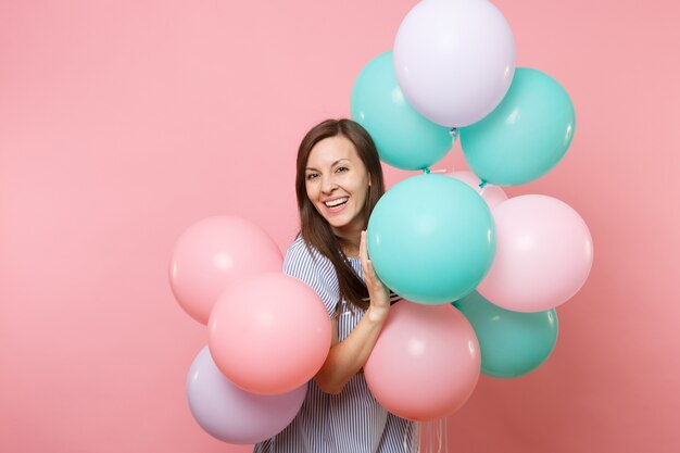 Portrait d'une belle jeune femme heureuse souriante vêtue d'une robe bleue tenant des ballons à air colorés isolés sur un fond rose tendance brillant. fête d'anniversaire, concept d'émotions sincères.