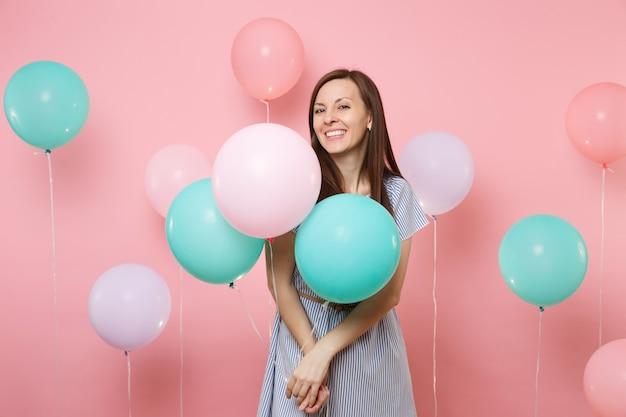Portrait de belle jeune femme heureuse souriante vêtue d'une robe à rayures bleues tenant des ballons à air colorés sur fond rose tendance lumineux. fête d'anniversaire, concept d'émotions sincères.