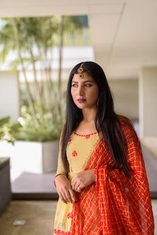 Portrait de belle jeune femme indienne portant des vêtements traditionnels à l'extérieur
