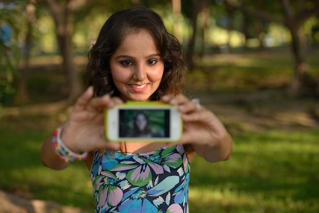 Portrait de la belle jeune femme indienne se détendre dans le parc en plein air