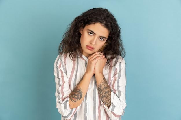 Portrait de belle jeune femme isolée sur fond de studio de couleur. notion d'émotions