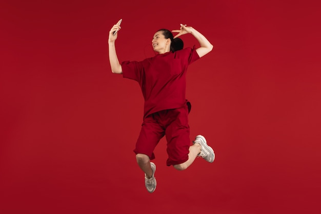 Portrait de belle jeune femme isolée sur fond de studio de couleur rouge. notion d'émotions