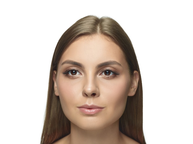 Portrait de la belle jeune femme isolée sur le mur blanc du studio.