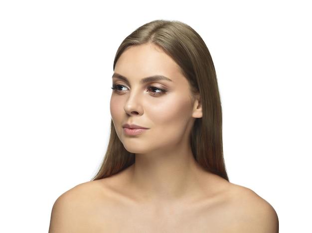 Portrait de la belle jeune femme isolée sur le mur blanc du studio