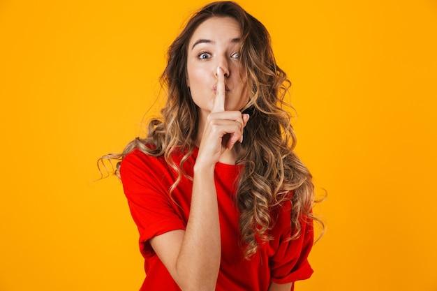 Portrait d'une belle jeune femme joyeuse debout isolée sur un mur jaune, montrant un geste de silence