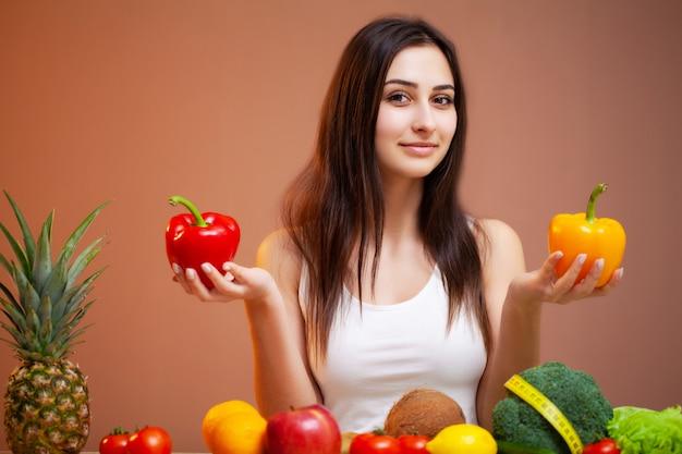 Portrait de la belle jeune femme avec des légumes, des fruits et un ruban à mesurer
