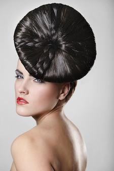Portrait de la belle jeune femme avec des lèvres rouges et une coiffure inhabituelle sur fond gris