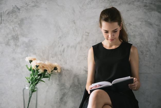 Portrait d'une belle jeune femme lisant livre relaxant dans le salon. images de style effet vintage.