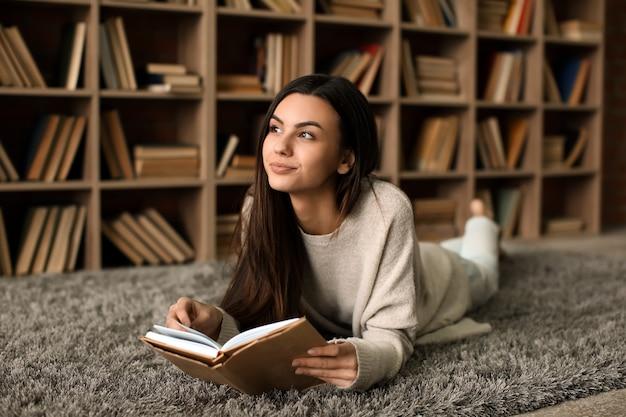 Portrait de la belle jeune femme avec livre dans la bibliothèque