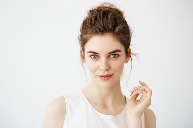 Portrait de la belle jeune femme ludique avec chignon posant.