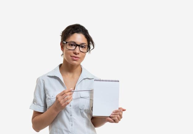 Portrait d'une belle jeune femme à lunettes avec un crayon et un bloc-notes