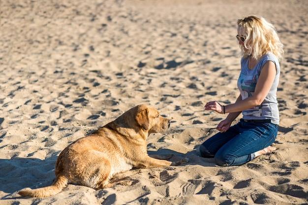 Portrait de belle jeune femme à lunettes de soleil assis sur la plage de sable avec chien golden retriever. fille avec chien au bord de la mer. bonheur et amitié. animal de compagnie et femme. femme jouant avec un chien au bord de la mer