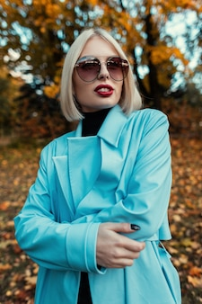 Portrait d'une belle jeune femme avec des lunettes de soleil dans un manteau bleu lumineux sur le fond d'un parc d'automne