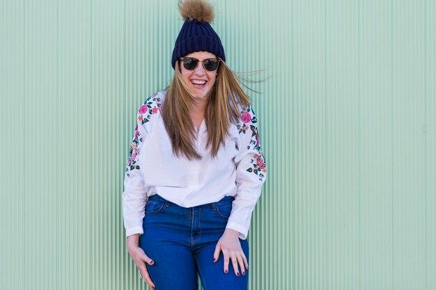 Portrait d'une belle jeune femme avec des lunettes de soleil modernes et chapeau, elle sourit mur vert