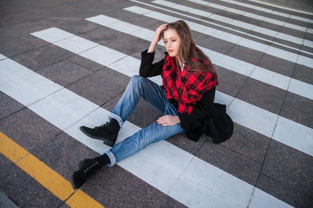Portrait de la belle jeune femme en manteau assis sur le passage pour piétons