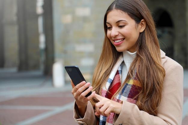 Portrait de la belle jeune femme avec manteau et écharpe en ville en tapant sur son téléphone