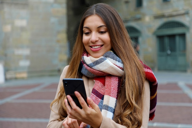 Portrait de la belle jeune femme avec manteau et écharpe en ville vérifiant son téléphone