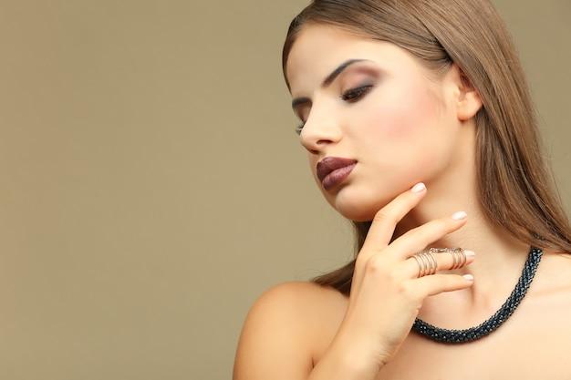 Portrait de belle jeune femme avec le maquillage professionnel sur le fond de couleur