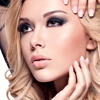 Portrait de la belle jeune femme avec un maquillage sombre des yeux. mannequin sur mur blanc.
