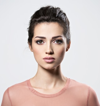 Portrait d'une belle jeune femme avec le maquillage des yeux charbonneux. jolie jeune fille adulte posant au studio. gros plan visage féminin attrayant.