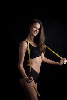 Portrait de la belle jeune femme mesurant sa taille avec un ruban à mesurer