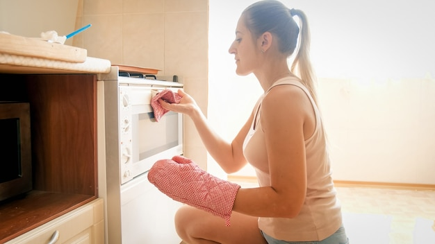 Portrait de belle jeune femme mettant le plat de cuisson avec des biscuits dans le four chaud à la cuisine