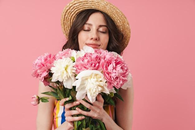 Portrait d'une belle jeune femme mignonne heureuse posant isolée sur un mur rose tenant des fleurs