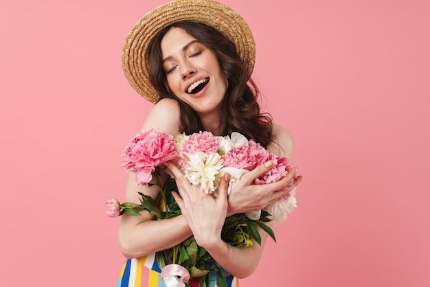 Portrait de la belle jeune femme mignonne souriante heureuse posant isolée sur un mur rose tenant des fleurs