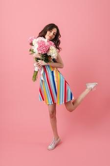 Portrait de la belle jeune femme mignonne souriante positive posant isolée sur un mur rose tenant des fleurs