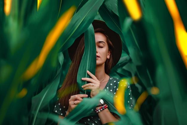 Portrait d'une belle jeune femme à la mode sensuelle et élégante avec une peau de visage lisse, des yeux fermés et un maquillage naturel portant un chapeau et une robe à pois tenant une feuille verte dans ses mains