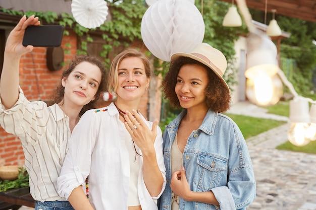 Portrait de la belle jeune femme montrant la bague de fiançailles prenant selfie avec des amis lors d'une fête en plein air