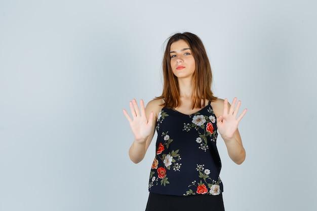 Portrait de la belle jeune femme montrant le geste d'arrêt en chemisier