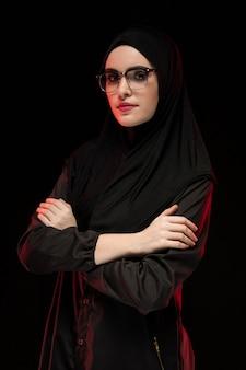 Portrait de la belle jeune femme musulmane branchée portant le hijab noir et des lunettes en tant que concept de mode orientale moderne posant noir