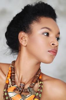 Portrait de la belle jeune femme noire avec collier africain traditionnel