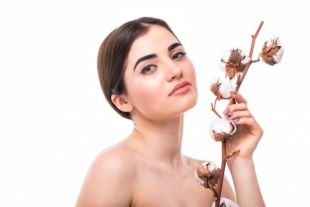 Portrait de la belle jeune femme avec une peau saine et avec des fleurs sur son épaule isolée