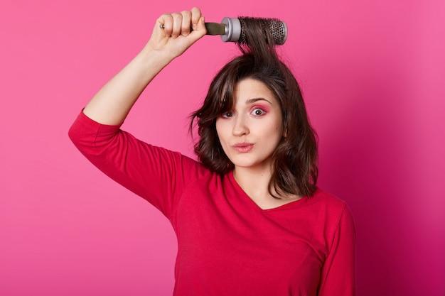 Portrait de la belle jeune femme peignant ses cheveux