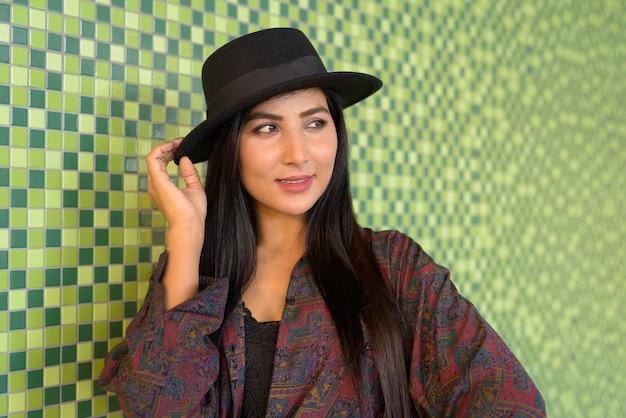 Portrait de belle jeune femme pensant contre le mur coloré