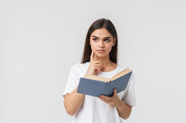 Portrait d'une belle jeune femme pensive casualy habillé debout isolé sur blanc, lisant un livre