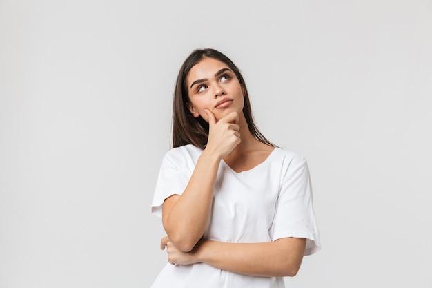Portrait d'une belle jeune femme pensive casualy habillé debout isolé sur blanc
