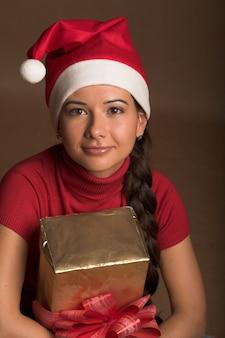Portrait de la belle jeune femme portant le chapeau de père noël avec le présent