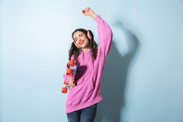 Portrait de belle jeune femme portant des écouteurs, écouter de la musique tout en tenant la planche à roulettes sur bleu en studio