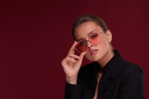 Portrait de la belle jeune femme portant des lunettes de soleil rouges. mannequin sensuel