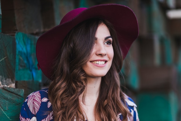 Portrait d'une belle jeune femme portant des vêtements décontractés et un chapeau moderne, debout sur fond de blocs de bois vert et souriant. mode de vie à l'extérieur.