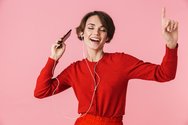Portrait d'une belle jeune femme portant des vêtements rouges debout isolé, écoutant de la musique avec des écouteurs et un téléphone mobile