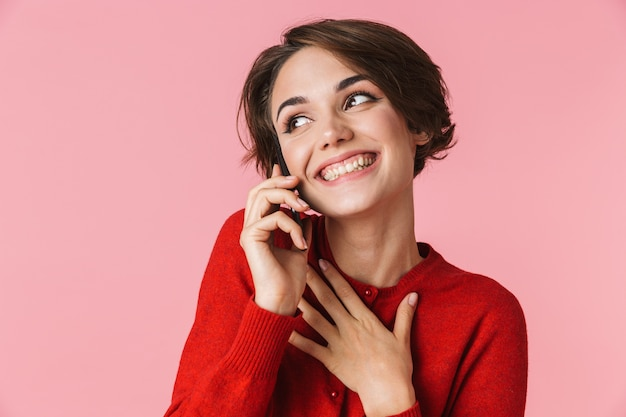 Portrait d'une belle jeune femme portant des vêtements rouges debout isolé, parler au téléphone mobile