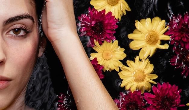 Portrait de la belle jeune femme posant avec des fleurs